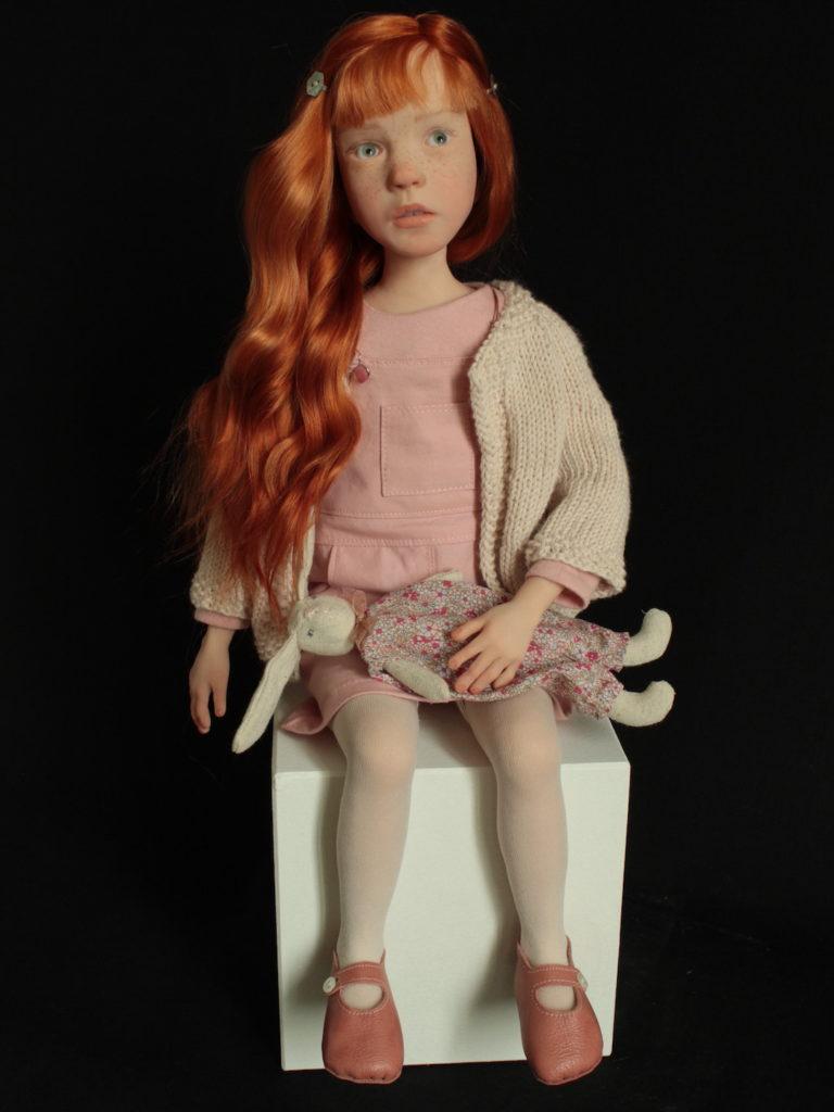 Petite fille rousse en rose assise sur un cube